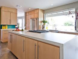 Light Brown Cabinets by Wooden Island With Grey Concrete Countertop Stainless Steel Tile