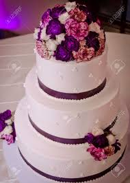purple and white wedding tiered white wedding cake with purple flowers ribbon stock photo