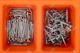 close up of different types of nails in an orange plastic box