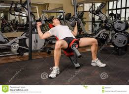 young man doing dumbbell incline bench press workout in gym stock