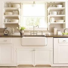 white kitchen farmhouse sink open shelves beadboard kitchen