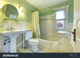 mint bathroom with light green curtains tile floor and wood plank