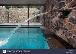 indoor swimming pool with fountain stream of water and stone