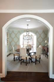 dining room crystal chandeliers archway leading to dining room with custom wallpaper and crystal