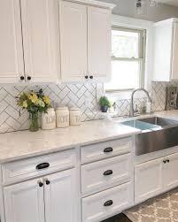 white kitchen cabinets with black hardware white herringbone patterned backsplash with chic black hardware for