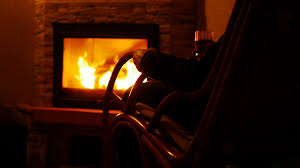 A Rocking Chair Man Sitting By The Fireplace In A Rocking Chair And With Glass Of