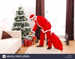 senior man in santa claus uniform putting a gift from bag under