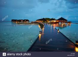 raised walkway leading to over water villas at night in the