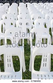 Plastic Stackable Lawn Chairs Row Of White Plastic Lawn Chairs In Front Of Train Boxcar Stock