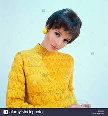 1960s brunette woman short pixie hair style yellow knit sweater
