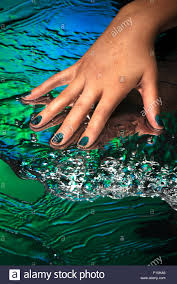 a hand with creative nail design on a green and blue water