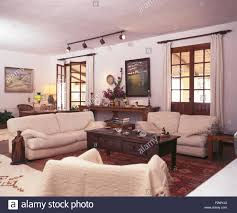 cream sofas and dark wood coffee table in white spanish living