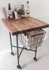 butcher block island w slide out basket on a steel pipe frame and