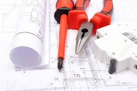 rolled electrical diagrams electric fuse and work tools lying