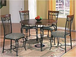 retro round wood and metal dining table with cushioned chairs of
