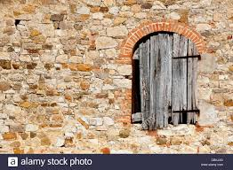 Tuscany House by Rustic Wall And Decaying Window Shutter Of An Old Farm House In