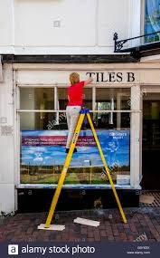 a woman on a step ladder removing a sign from above a shop the