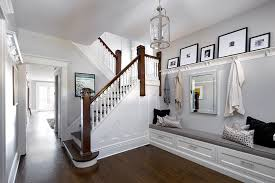 foyer with picture ledge with hooks over built in bench