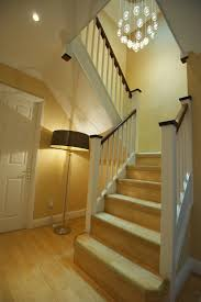 hall and stairs lighting white trim white spindles dark hand rail house update ideas
