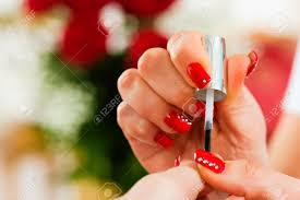 woman in a nail salon receiving a manicure by a beautician lots