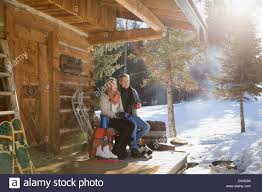 couple sitting on cabin porch in winter stock photo royalty free