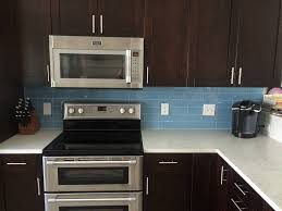 sky blue glass subway tile kitchen backsplash with dark cabinets