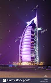 the sail shaped burj al arab hotel lit by colorful lights at night