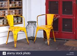 two colorful yellow weathered metal chairs on a porch set against