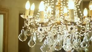 Cleaning Chandelier Crystals Cleaning Lady Dusting Chandelier With Feather Duster Stock Footage