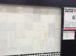 Installing a new cararra marble tile backsplash in the kitchen