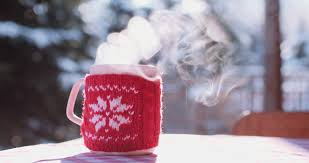 steaming cup of coffee or tea standing on the outdoor table in
