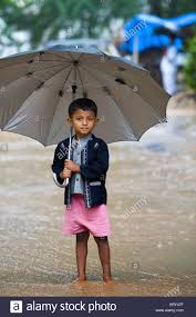 small indian boy with big umbrella in the rain stock photo
