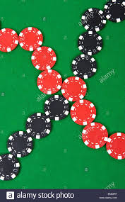 poker table top and chips crossed lines of red and black poker chips on green poker table top