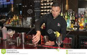 martini shaker shaking handsome bartender shaking drink in a cocktail shaker stock