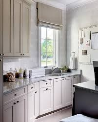 light gray laundry cabinets with gray granite countertops