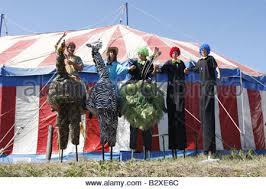 clown stilts of in clown costumes walking on stilts blue