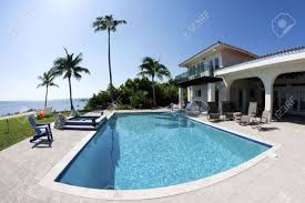 beautiful swimming pool with palm tree and a house in tha florida