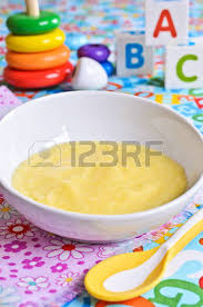 liquid baby food yellow color on the plate on the background