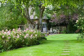 English Cottage Gardens Photos - english cottage garden with small patio in summer stock photo