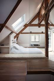 glass enclosed shower bath combination in a modern home in a platform bed is tucked into the eaves of an attic with exposed beams