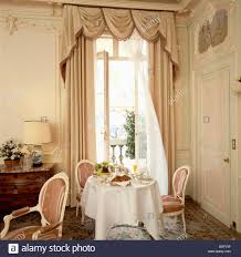 Circular Table by Circular Table With White Cloth In Front Of French Windows With
