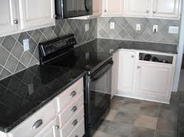 backsplash for black and white kitchen kitchen daltile granite uba tuba on white cabinets with
