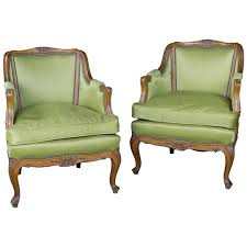 pair of louis xv style green armchairs with exposed wood frame for