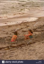 two little girls siting in a hole in the sand on a beach in
