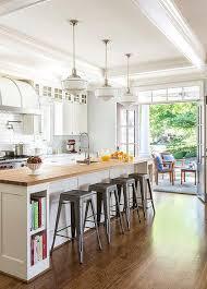 white kitchen island with stools three schoolhouse pendants illuminate a white kitchen island fitted