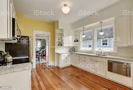 yellow kitchen wood cabinets kitchen interior with white cabinets yellow walls and wood floor stock photo image now