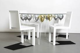 suspended by shiny gold and silver balloons up dining table