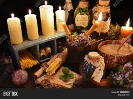 halloween text symbols witch table with burning candles magic objects and healing herbs