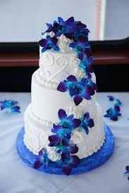 round white wedding cake with swirls and blue orchid flowers