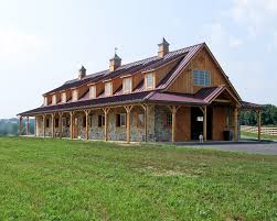 horse barn with red metal roof and stone wainscotting stables